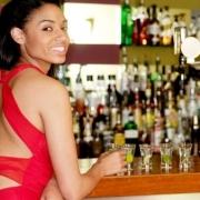 zvodná žena v červených šatách stojí pri bare
