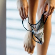 ruky naťahujujúce nohavičky na ženké nohy