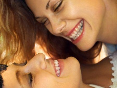 tváre dvoch žien, ktoré ležia oproti sebe a smejú sa