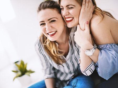 dve ženy sa smejú, túlia sa k sebe a chytajú sa za ruky