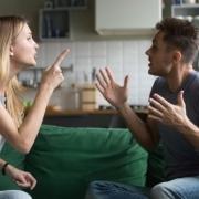 dvojica v hádke na gauči gestikuluje rukami