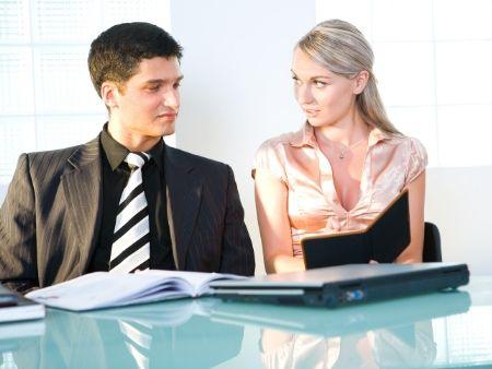 muž a žena sedia v kancelárii za jedným stolom
