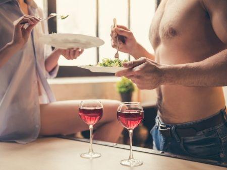 dvojica s taniermi v rukách a s vínom na stole