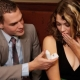muž núka žene prsteň v krabičke