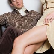 žena sedí mužovi na kolenách a odhŕňa si sukňu