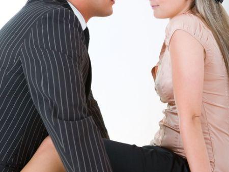 žena sedí na stole, muž oproti nej, iba telá