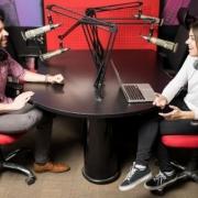 muž a žena sedia oproti sebe a vysielajú v rádiu