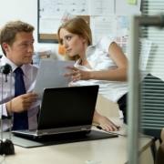 žena leží na stole a flirtuje s mužom za počítačom