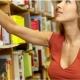 žena v vyberá knihu z políc