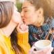 dve ženy držia kávu a bozkávajú sa na ústa