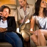 letuška ukazuje páru, ktorý sedí vzadu v lietadle doklady