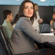 ľudia sedia za počítačmi v kancelárii a žena sa obzerá