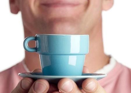 chlap ponúka malú kávičku v malom nádobíčku