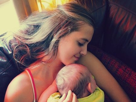 tvár mladej ženy s novorodencom