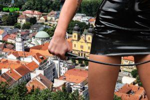 sado maso žena s bičíkom v ruke, v pozadí Mierové námestie v Trenčíne
