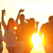 partia mladých ľudí sa zabáva na pláži pri západe slnka