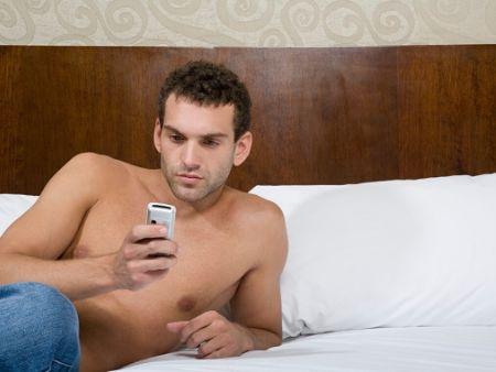 muž na posteli číta z mobilu