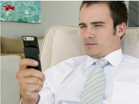 muž číta z mobilu