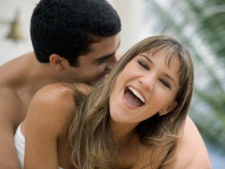 muž drží odzadu ženu, ktorá sa smeje