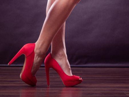 oholené nohy v červených topánkach