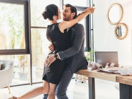 muž sa opiera o stôl a žena ho objíma