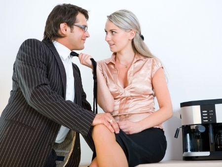 žena sedí na stole, ťahá muža za kravatu a on ju drží za koleno