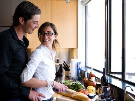žena krája jedlo v kuchyni a muž ju odzadu objíma