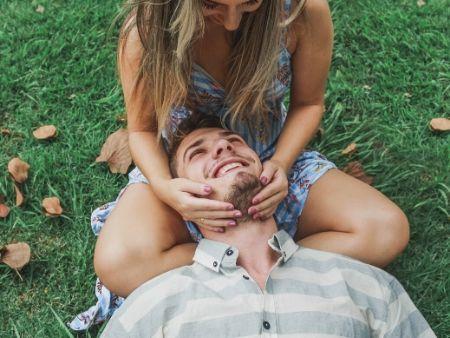 muž leží s hlavou v ženinom klíne a sú na lúke