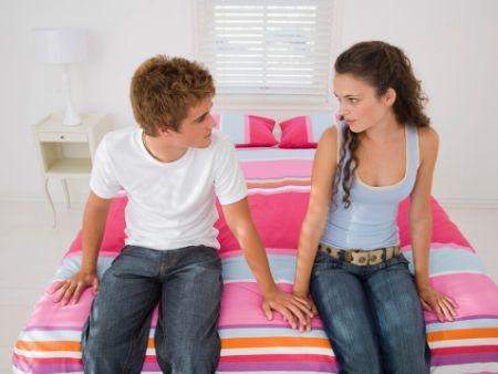 chlapec a dievča sedia na posteli a pozerajú sa na seba