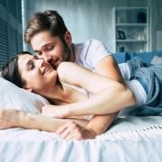 muž a žena oblečení v posteli