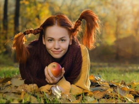žena s ryšavými vrkočmi a jablkom v ruke leží na lístí v záhrade