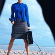 žena v kostýme s kufríkom drží v ruke dlhý bič