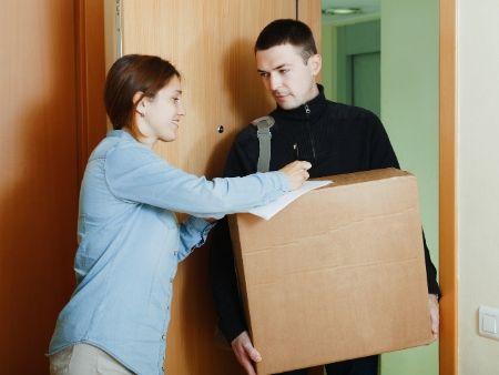 poštár odovzdáva balík žene