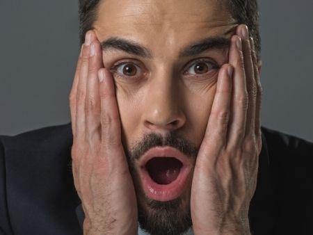 tvár prekvapeného muža s rukami na tvári