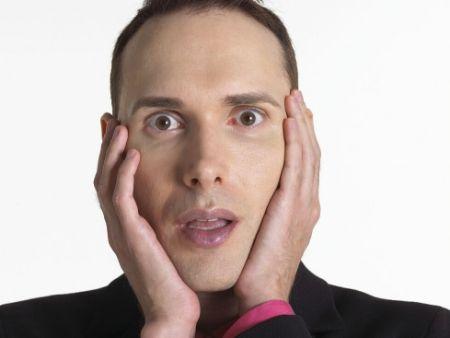 tvár prekvapeného muža s rukami na lícach