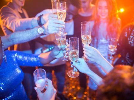 ruky, ktoré si pripíjajú na párty