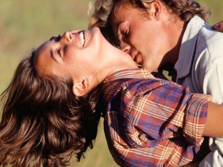 žena sa smeje so zaklonenou hlavou a muž ju bozkáva na krk v prírode