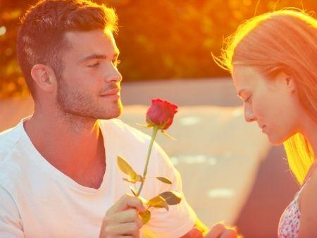 muž podáva žene ružu