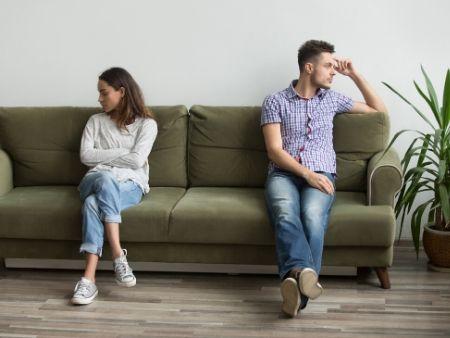 rozhádaný pár sedí na gauči a každý sa pozerá na inú stranu