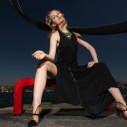 žena v čiernych šatách sedí s roztiahnutými nohami