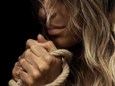 tvár ženy so zviazanými rukami