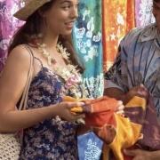 ryšavá žena v klobúku ukazuje látku mužovi