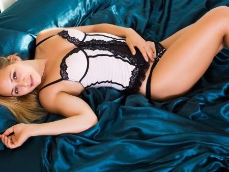žena leží v erotickej bielizni a ruku má na bruchu