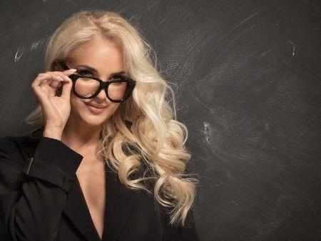 sexy blondína v okuliaroch s výstrihom pri tabuli