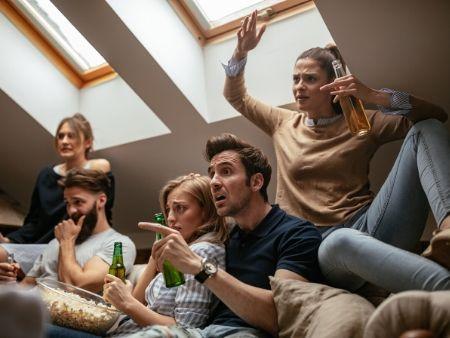 skupina mladých ľudí sleduje TV prenos