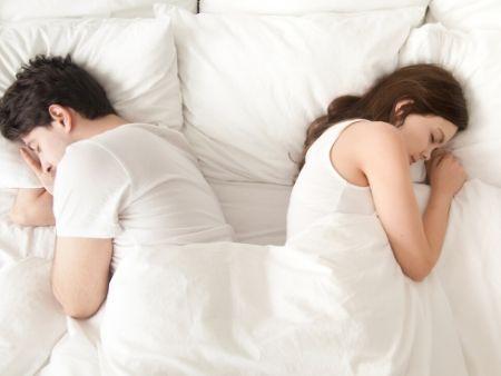 dvojica spí v posteli schúlená chrbtom od seba