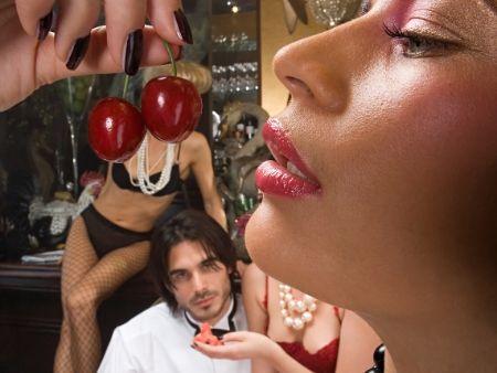 jedna zo žien v erotickom prádle si dáva do úst čerešne