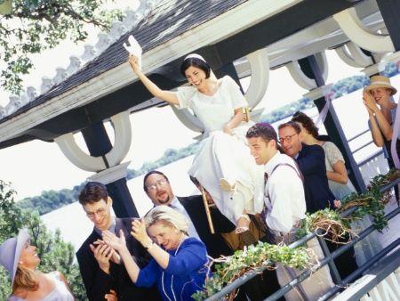 svadobčania nesú nevestu na stoličke