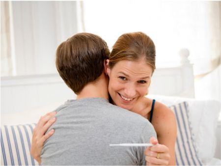 žena s tehotenským testerom sa teší za mužovým chrbtom