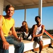 traja mladí ľudia sedia pri chate